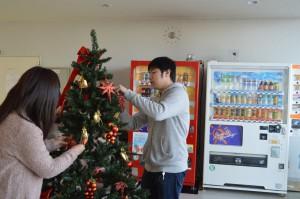 ツリーの飾りつけをする学生たち